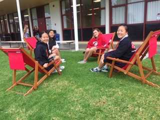 Students enjoy the new Rosary lawn furniture before class.  Photo by Ms. Barclay