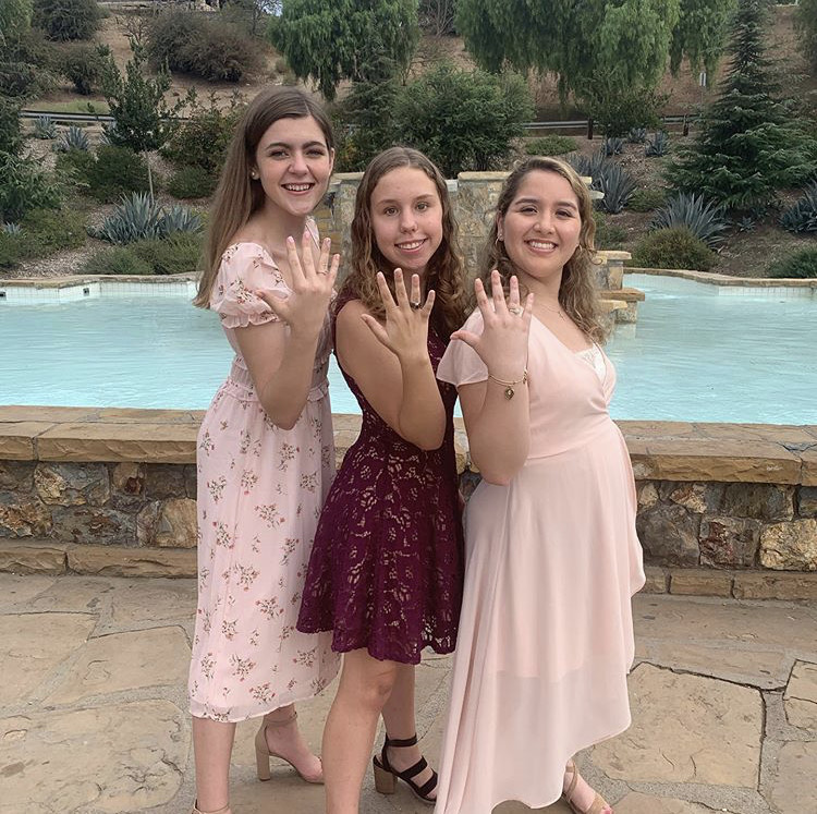 Katie Thomas '22, Julia Herman '22, and Giovana Watson '22 (left to right) posing with their new class rings after the Rosary Day ceremony Photo Credit: Giovana Watson