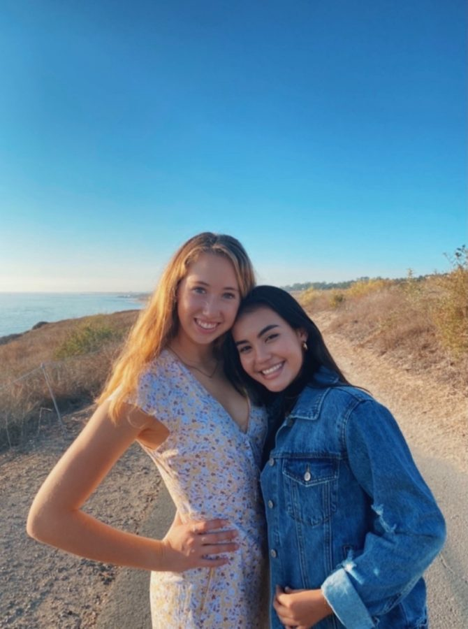 Adriana Arroyo' 23 and Elena Walz' 22 smiling for a picture at the beach.