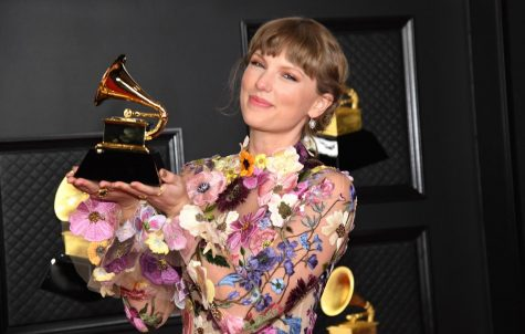 Taylor Swift posing with her Album of the Year award at the 2021 Grammys. Photo by Kevin Mazur