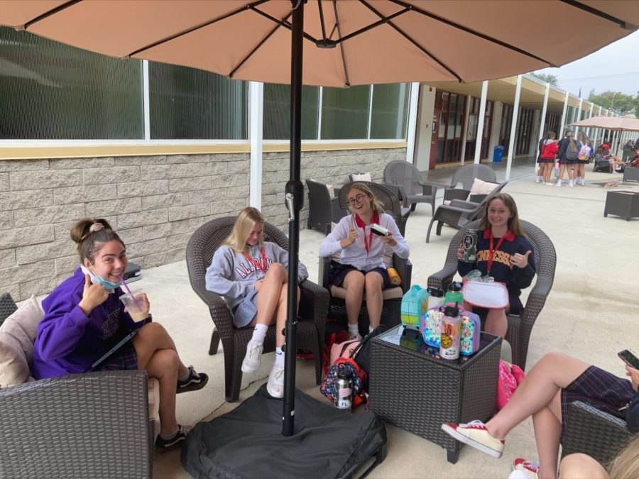 Seniors Lily Demman, Daly Holman, Kate Curry, and Elizabeth Walloch (left to right) enjoying social time and snacks on the new patio furniture. Photo Credit: Anna DiCrisi